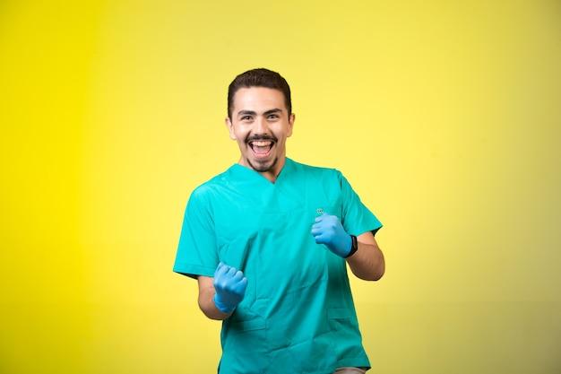 Doktor in grüner uniform und handmaske lächelt und zeigt sein glück.