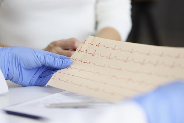 Doktor in handschuhen hält patienten-kardiogramm-nahaufnahme