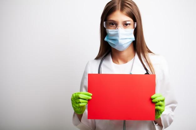 Doktor in handschuhen, maske und brille hält eine leere form mit platz für text