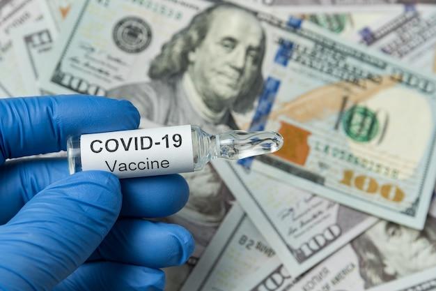 Doktor in medizinischen handschuhen, die medizinflasche mit etikett covid-19 auf geld halten. ampulle mit impfstoff gegen coronavirus.