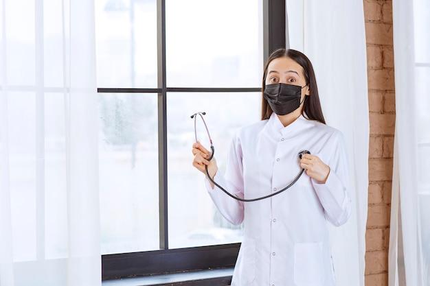 Doktor in schwarzer maske mit einem stethoskop, das am fenster steht und den herzschlag überprüft.