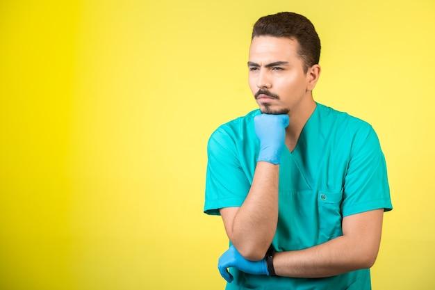 Doktor in uniform und handmaske, der etwas ansieht und überdenkt.