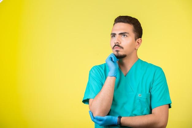 Doktor in uniform und handmaske, der nach nirgendwo schaut und überdenkt.