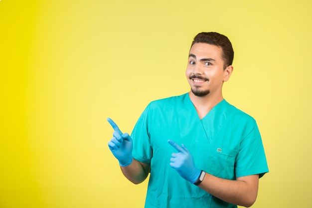 Doktor in uniform und handmaske zeigt etwas darüber.