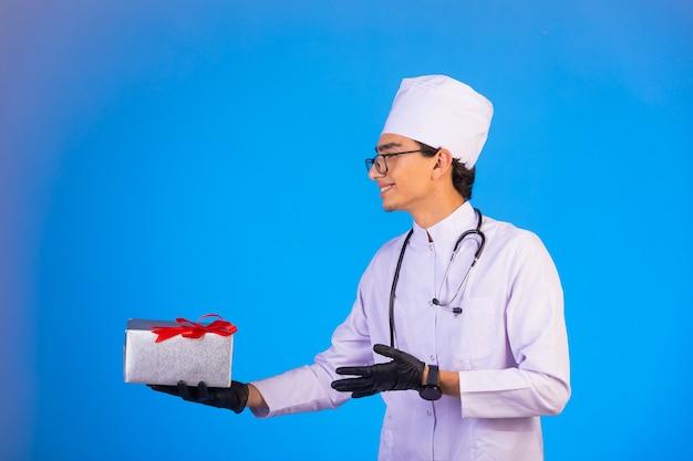 Doktor in weißer medizinischer uniform, die eine geschenkbox hält und sich bei jemandem bedankt.