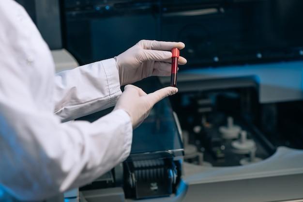 Doktor in weißer medizinischer uniform mit rotem reagenzglas