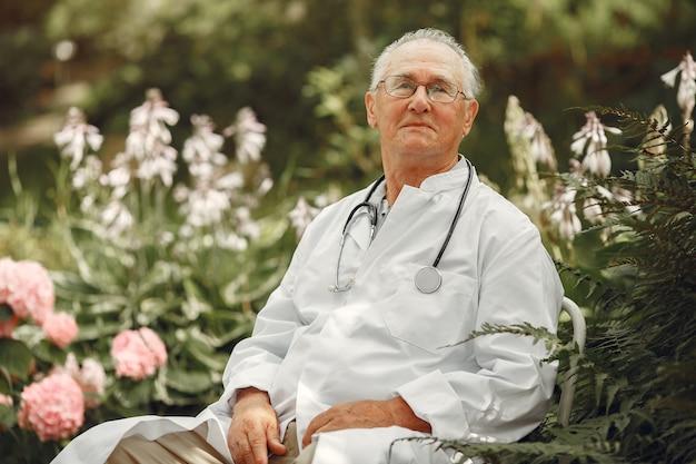 Doktor in weißer uniform. alter mann, der in einem sommerpark sitzt. senior mit stethoskop.