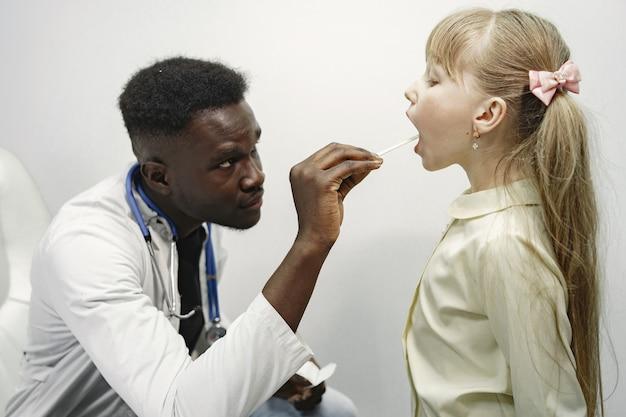 Doktor in weißer uniform. mann mit stethoskop. mädchen mit langen haaren.