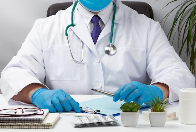 Doktor in weißer uniform sitzt an einem weißen tisch und schreibt in a
