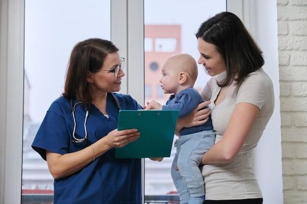 Doktor kinderarzt im gespräch mit junger mutter hält ihr baby in den armen