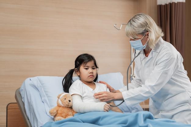 Doktor kinderarzt untersucht eine kleine patientin auf dem bett