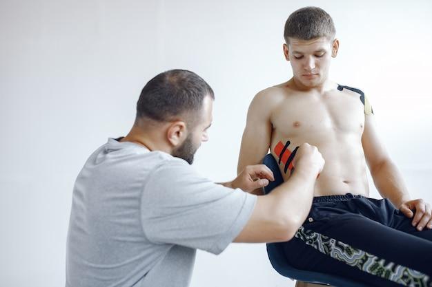 Doktor klebt einen tipi an einen athleten im krankenhaus