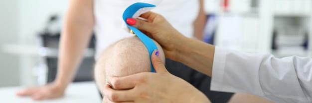Doktor klebt kinesio-klebeband auf mann auf seiner knie-nahaufnahme