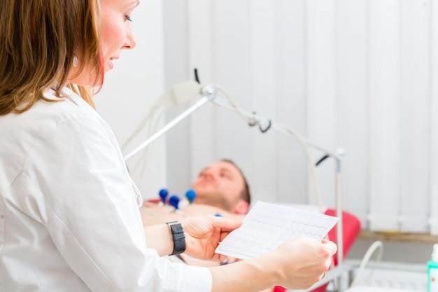 Doktor kontrolliert patienten ekg in arztpraxis