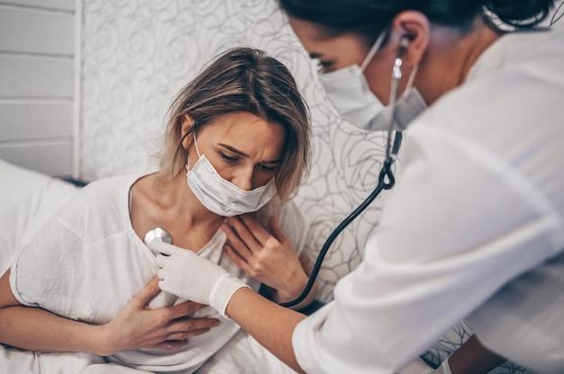 Doktor krankenschwester in schützender gesichtsmaske, die mit einem stethoskop auf atem hört