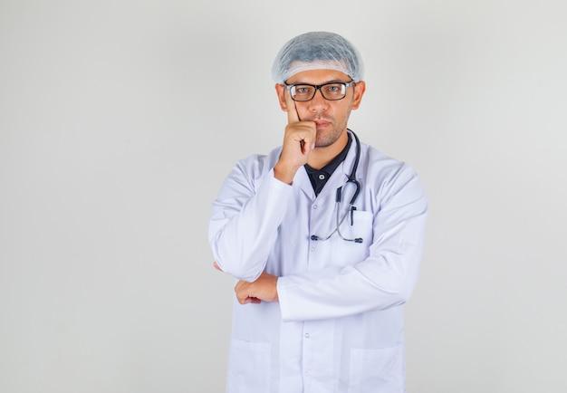 Doktor legte finger auf seine wange in weißem mantel und hut und sah positiv aus