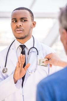 Doktor lehnt ein bestechungsgeld im krankenhaus ab.
