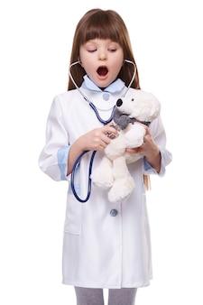 Doktor-mädchen im weißen medizinischen mantel hört auf herzschläge mit stethoskop am spielzeugbären auf weißem lokalisiertem hintergrund