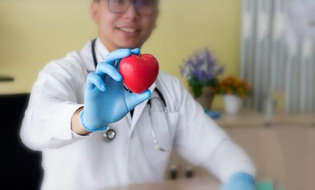 Doktor mit dem stethoskop, das herz in seiner hand hält.