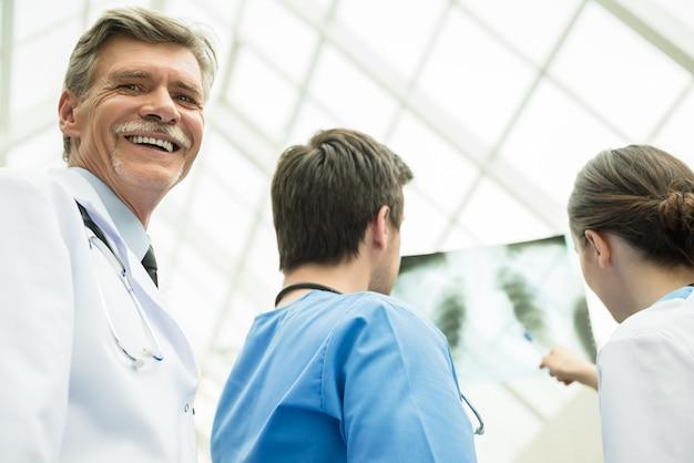 Doktor mit den medizinischen internierten, die zusammen röntgenstrahl betrachten.