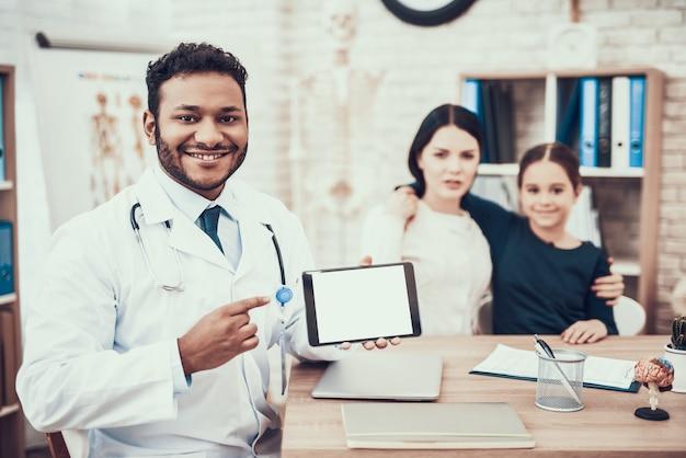 Doktor mit der tablette, die kamera und das lächeln betrachtet.