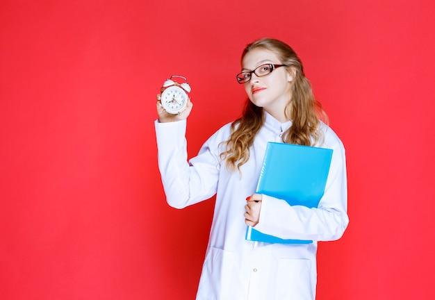 Doktor mit einem blauen ordner, der eine uhr hält.