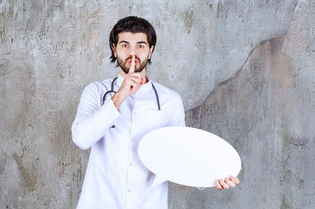 Doktor mit einem stethoskop, das eine ovale leere infotafel hält und um ruhe bittet.