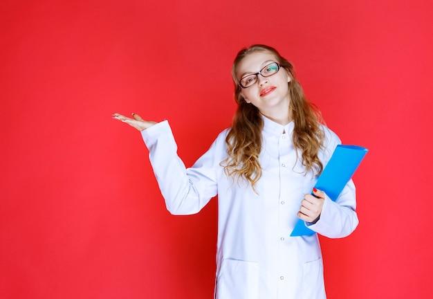 Doktor mit einer blauen mappe, die auf irgendwo oder jemanden zeigt.