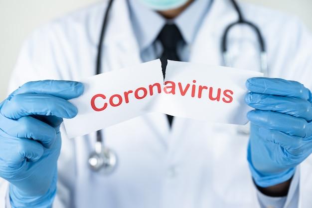 Doktor mit einer stethoskophand, die roten text auf weißem papier mit dem wort coronavirus hält