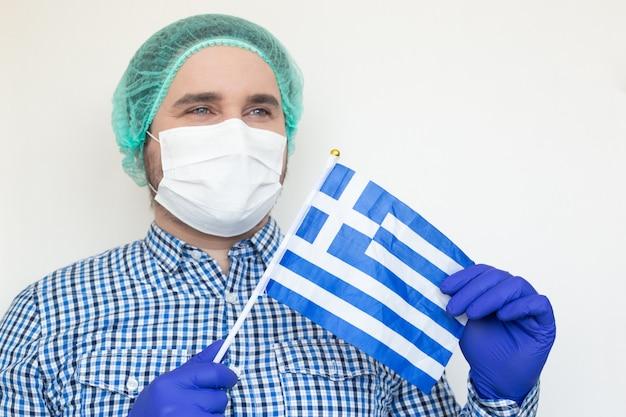 Doktor mit griechischer flagge in seinen händen.