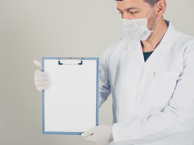 Doktor mit handschuhen, die papierhalter vertikal suchen und halten. seitenansicht.