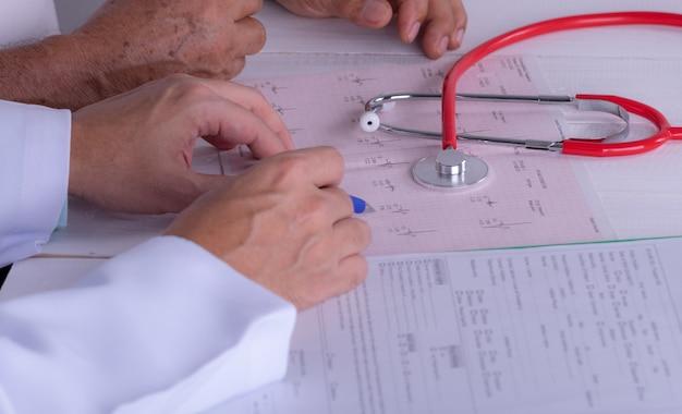 Doktor mit kardiogrammdiagramm. kardiologe, der seine geduldigen ekg-ergebnisse erklärt.