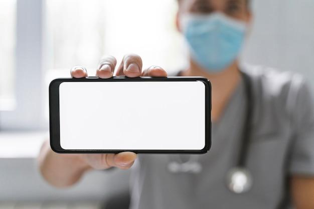Doktor mit medizinischer maske, die smartphone hält