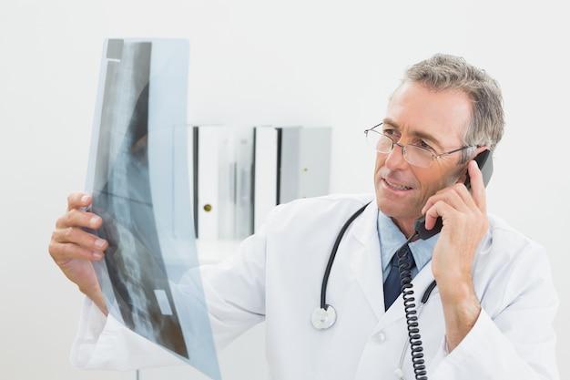Doktor mit röntgenstrahlbild bei der anwendung des telefons im büro
