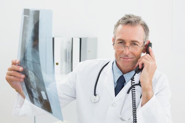 Doktor mit röntgenstrahlbild unter verwendung des telefons im büro