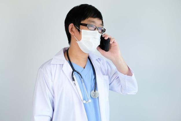 Doktor mit schutzmaske im gespräch mit smartphone