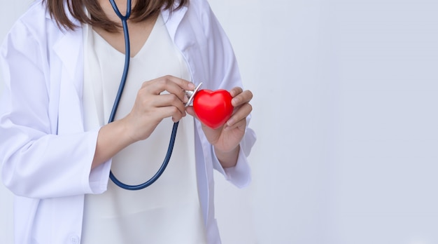 Doktor mit stethoskop rotes herz überprüfend