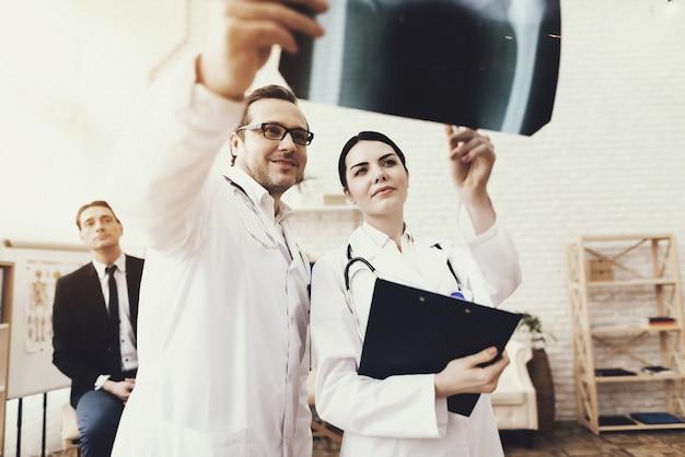 Doktor mit stethoskop und krankenschwester, die röntgenstrahl überprüfen.