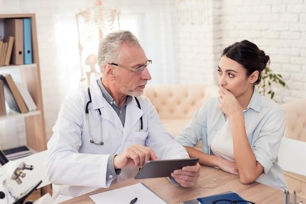 Doktor mit stethoskop und weiblichem patienten im büro.