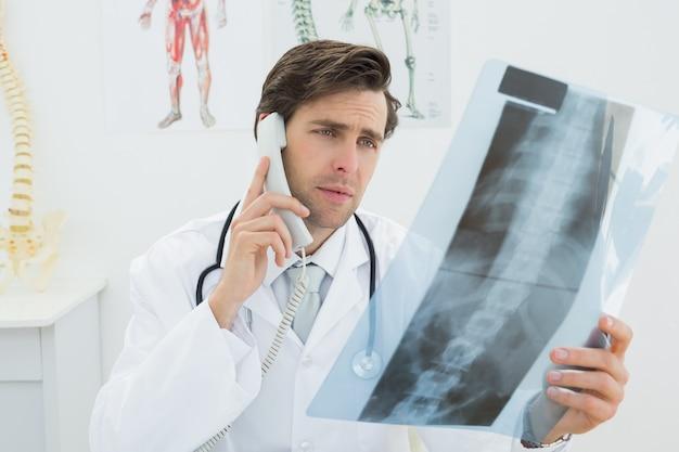 Doktor mit wirbelsäulenröntgenstrahlbild unter verwendung des telefons
