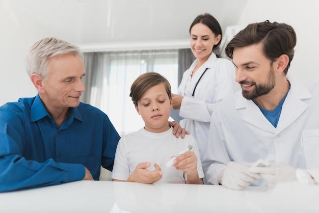 Doktor nimmt blut für diabetesanalyse von einem jungen sohn.