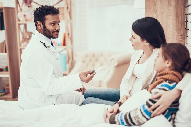Doktor nimmt temperatur des mädchens mit schwangerer mutter.