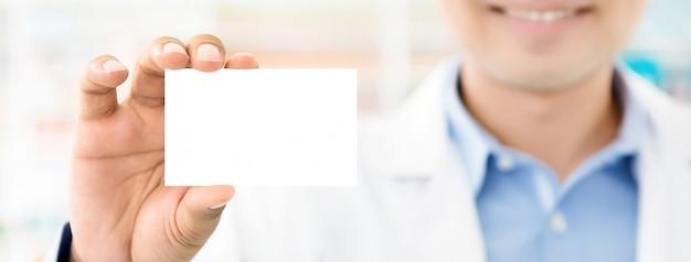 Doktor oder medizinische arbeitskraft, die leere visitenkarte zeigen