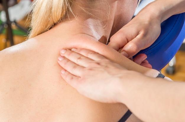 Doktor, physiotherapeut, der zurück ihren patienten überprüft und dekontrahierende massage tut.
