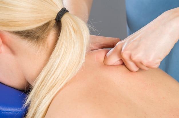 Doktor, physiotherapeut, der zurück ihren patienten überprüft und dekontraktierende massage tut.