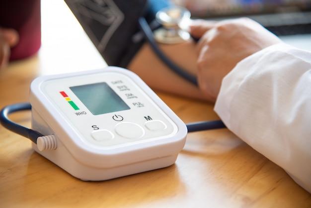 Doktor pressure gauge patient mit doktor, der blutdruck von ihrem patienten misst