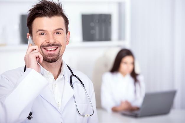Doktor schaut in die kamera, während er telefonisch spricht.