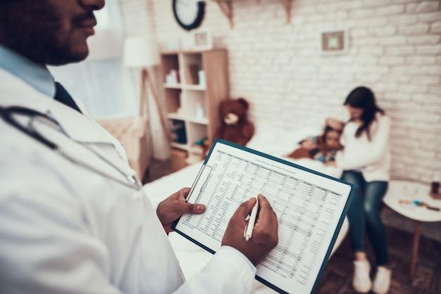 Doktor schreibt auf klemmbrett mit schwangerer mutter