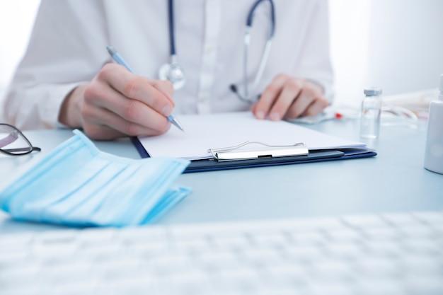 Doktor schreibt eine verordnung, während er am tisch sitzt.