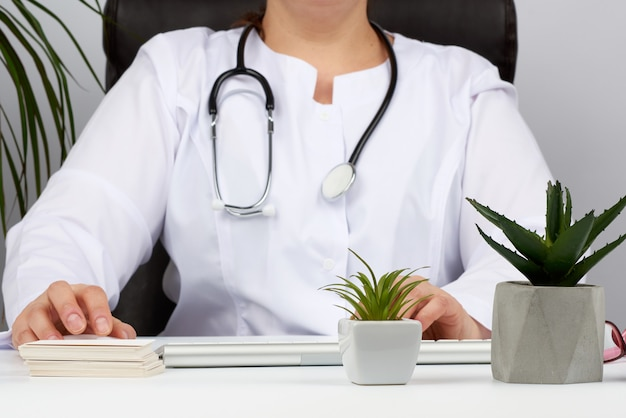 Doktor sitzt an einem weißen tisch in einer weißen uniform